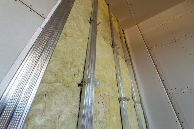 Mur d'une pièce en rénovation avec isolation en laine de roche minérale et cadre métallique préparé pour plaques de plâtre.