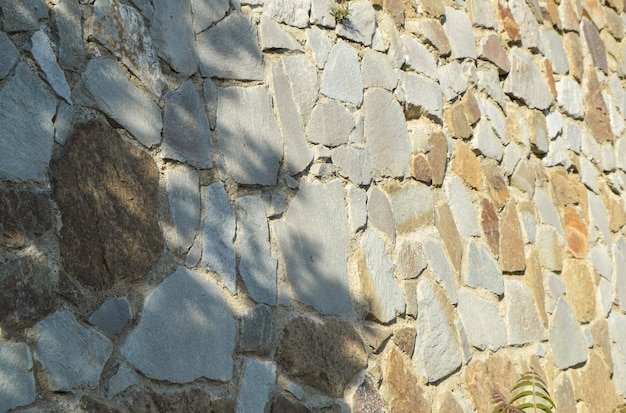 Mur de pierre authentique, clôture en pierre et ciment, journée d'été ensoleillée et ombres sur le mur.