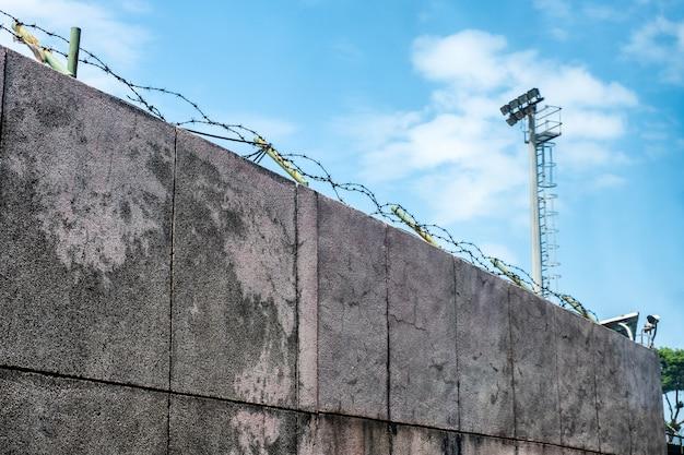 Mur en pierre avec bobines de fil de fer barbelé et caméra de sécurité