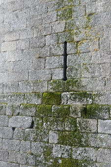 Mur de pierre du château de guimaraes détail de fenêtre très étroite et de mousse qui a poussé à cause des années passées sur des briques en pierre avec copie espace