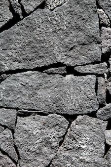 Mur de pierre volcanique en pierre de lave noire