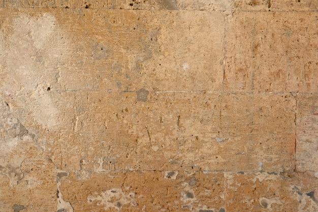 Mur de pierres rectangulaires jaunes avec du ciment, fragment d'architecture ancienne