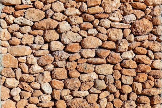 Mur pierreux construit de pierres de différentes formes et tailles, structure de mur pierreux
