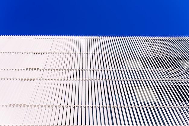 Mur avec des planches en métal blanc et fond de ciel bleu et espace négatif.