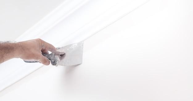 Mur de plâtrage avec couteau à mastic. rénovation