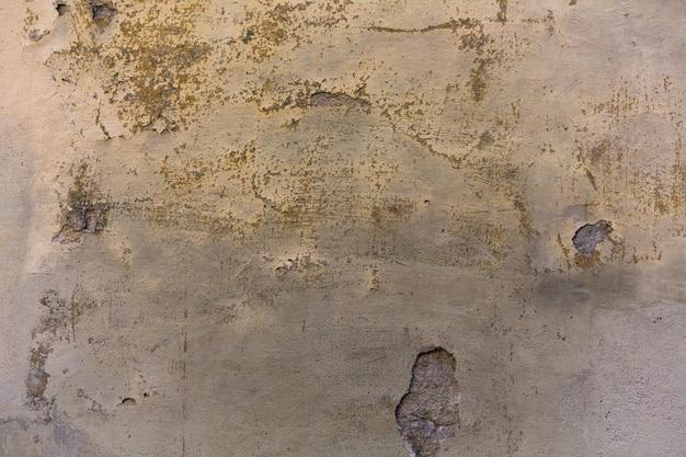 Mur plâtré grunge avec des fissures