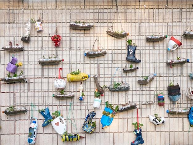 Mur rempli de pots de fleurs fabriqués avec des bouteilles en plastique, à l'extérieur, fabriqués par des écoliers