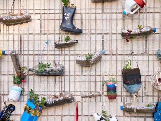 Mur rempli de pots de fleurs fabriqués avec des bouteilles en plastique, fabriqués par des écoliers, à l'extérieur