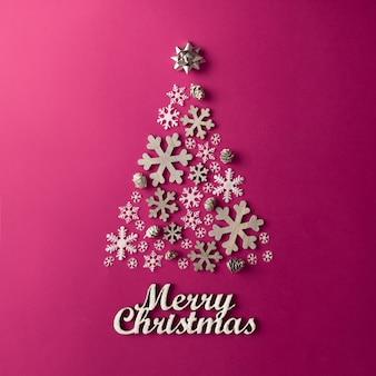 Mur rose de noël et du nouvel an avec arbre de noël en flocons de neige. concept de vacances. mise à plat.