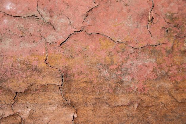 Mur rouge avec des fissures, arrière-plan
