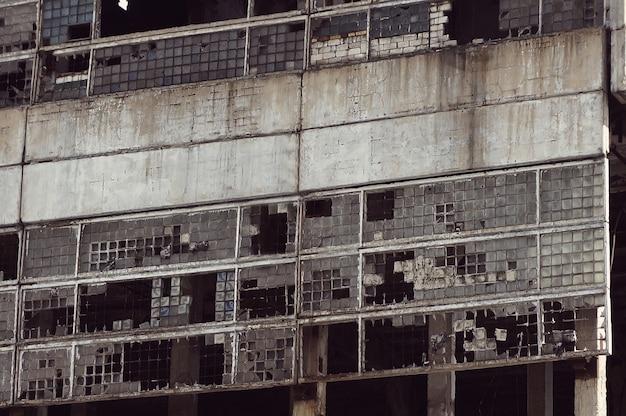 Mur en ruine d'une plante. verre cassé dans les fenêtres de la vieille maison
