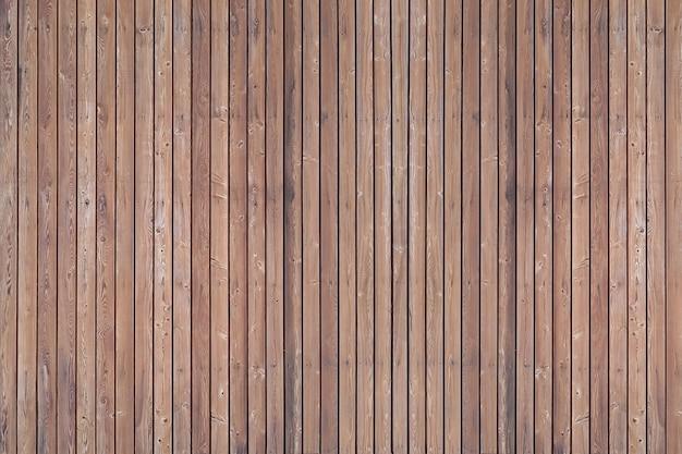 Un mur solide de planches de bois brun vieilli avec des clous bouchés situés verticalement.