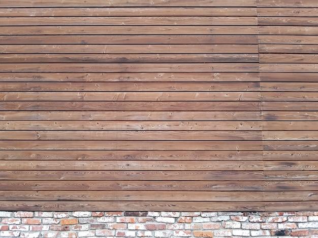 Un mur solide de planches de bois brun vieilli avec des clous martelés situés horizontalement sur une fondation en brique.