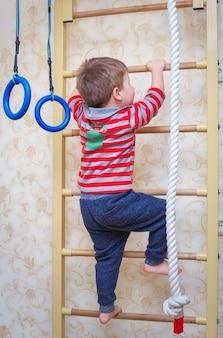 Mur suédois de sports pour enfants de gymnastique. l'enfant monte les escaliers.