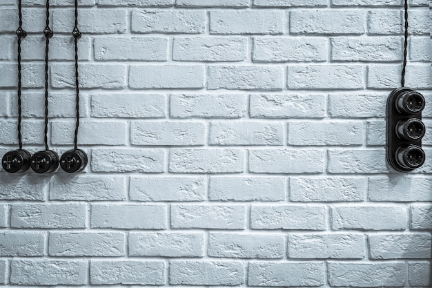Mur texturé en brique blanche, avec prises, interrupteurs et câblage électrique. fond élégant rustique