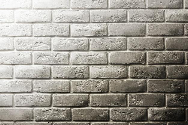 Mur texturé en brique blanche, transition dégradée vers une brique sale noire