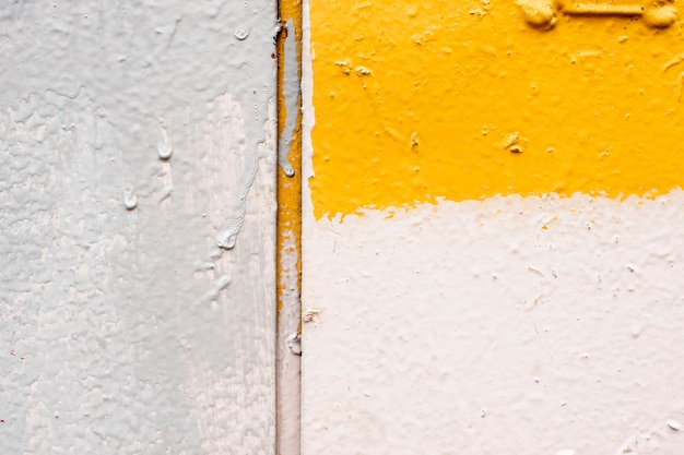 Mur de texture, peinture goutte à goutte, mastic, mur blanc et jaune
