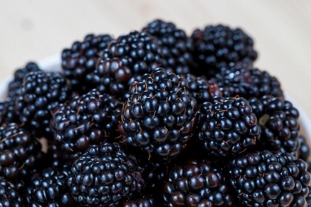 Les mûres fraîches noires sur le tas au moment de la récolte, gros plan