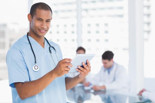 Murgeon à l'aide de tablette numérique avec groupe autour de la table à l'hôpital