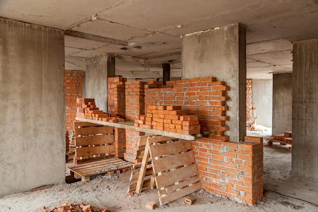 Murs d'une maison en brique rouge à plusieurs étages outils de chantier brouette sable et briques