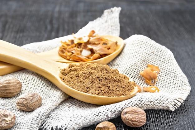 Muscade moulue et arillus de muscade séchée dans deux cuillères, noix entières sur toile de jute sur un fond de planche de bois sombre