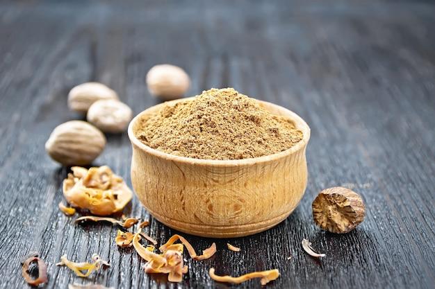 Muscade moulue dans un bol, noix entières et arillus de muscade séchée sur un fond de planche de bois