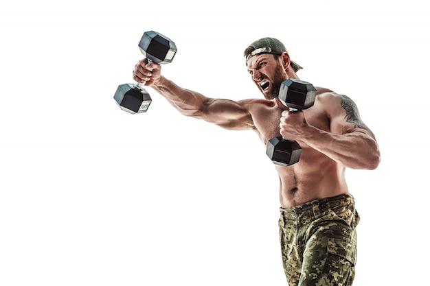 Musclé homme athlète bodybuilder en pantalon de camouflage avec un torse nu frappant avec des haltères comme un boxeur
