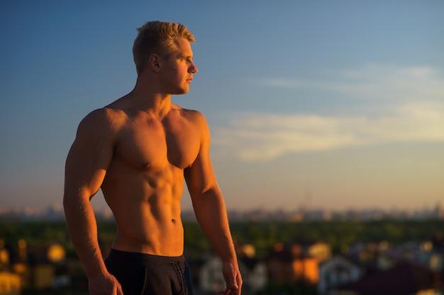 Musclé jeune homme debout sur le toit et regardant pendant le coucher du soleil. concept de mode de vie sain et confiant.