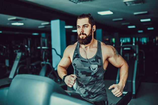 Muscle man en cours d'exécution sur tapis roulant.