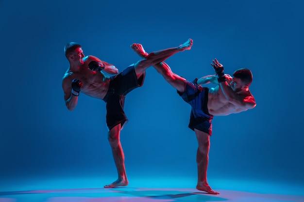 Musclé. mma. deux combattants professionnels poinçonnant ou boxant isolés sur fond bleu studio en néon. ajustez les athlètes ou les boxeurs caucasiens musclés qui se battent. sport, compétition et émotions humaines, annonce.