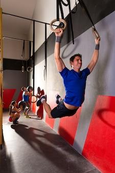 Muscle ups sonne homme se balançant d'entraînement au gymnase