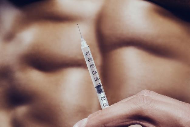 Muscles d'injection de seringue stéroïde bodybuilder homme fort