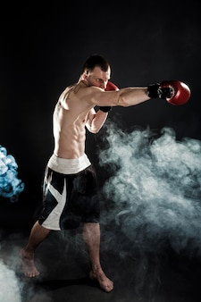 Musculaire muay thai fighter punching in smoke
