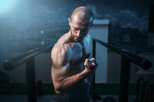 Muscular sports man exercices avec élastique en caoutchouc.