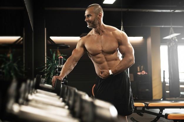 Musculation et remise en forme. bodybuilder musculaire dans une zone de poids libres dans le gymnase