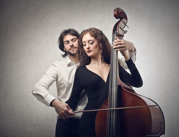 Un musicien apprend à un étudiant à jouer de la contrebasse