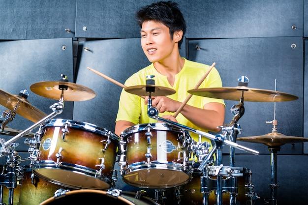 Musicien asiatique batteur en studio d'enregistrement