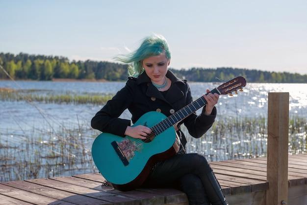 Un musicien aux cheveux bleus et une guitare bleue est assis sur une passerelle du lac et joue de la musique.