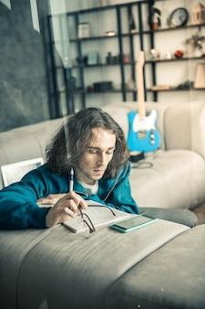 Musicien coincé. beau mec paisible enlevant des lunettes et réfléchissant à son travail tout en s'appuyant sur un canapé confortable
