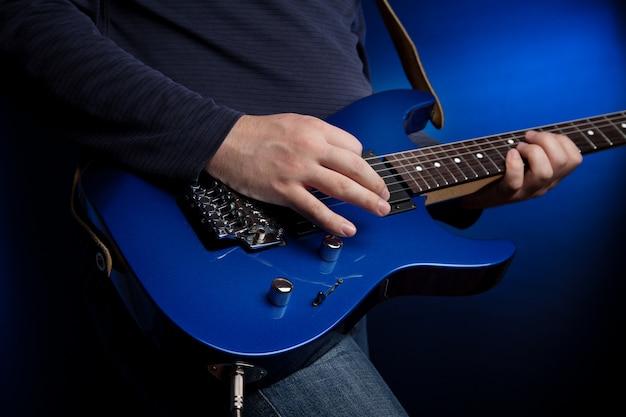 Musicien guitariste rock jouant une guitare bleue