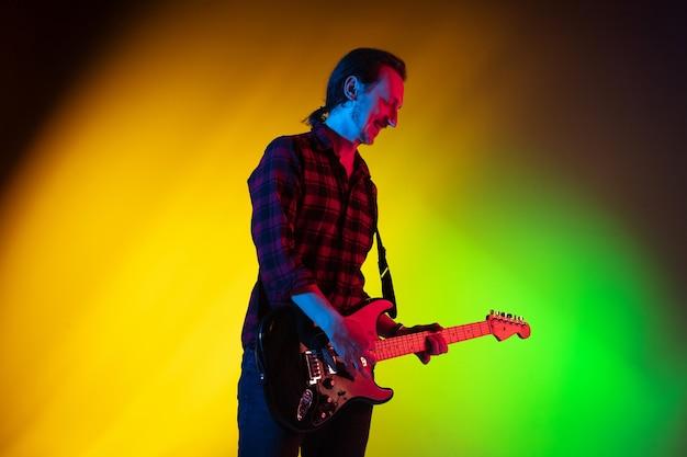Musicien homme jouant de la guitare sur la lumière au néon