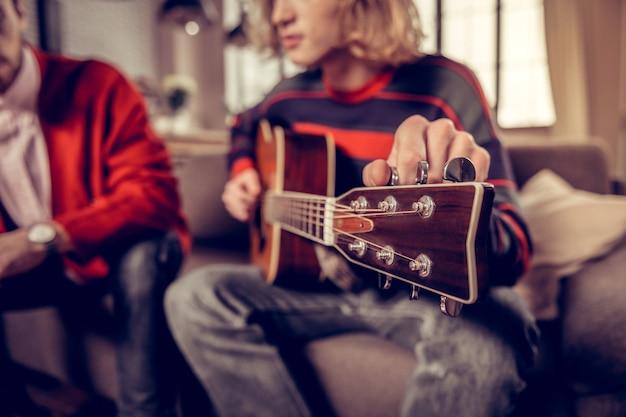 Musicien jouant. gros plan d'un musicien aux cheveux blonds portant un pull jouant de la guitare à la maison
