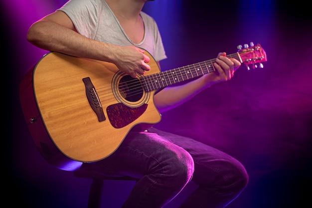 Le musicien joue de la guitare acoustique.
