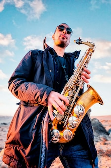 Musicien latin jouant du saxophone dans le désert à atacama au chili