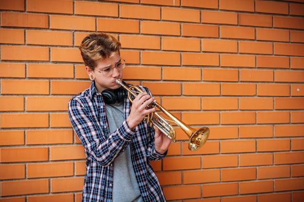 Musicien mâle vue de côté en élégant chapeau et lunettes de vue jouant de la trompette