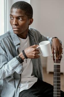 Musicien masculin avec guitare et tasse