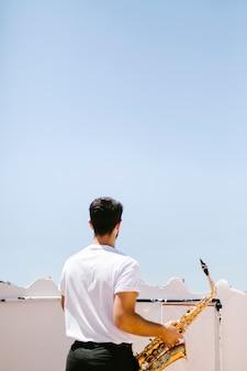 Musicien moyen vue arrière tenant sax
