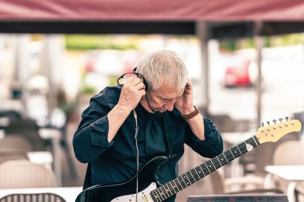Musicien préparant le microphone pour jouer dans la scène d'une terrasse
