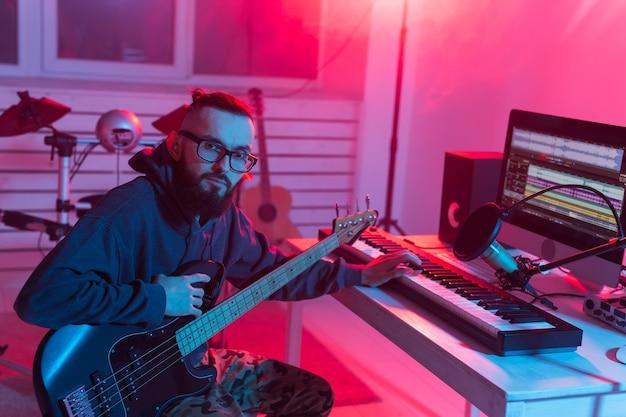 Musicien professionnel enregistrant la guitare en studio numérique à la maison, technologie de production musicale