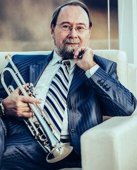 Musicien professionnel avec une trompette assis sur une chaise, sur le fond de la salle de concert